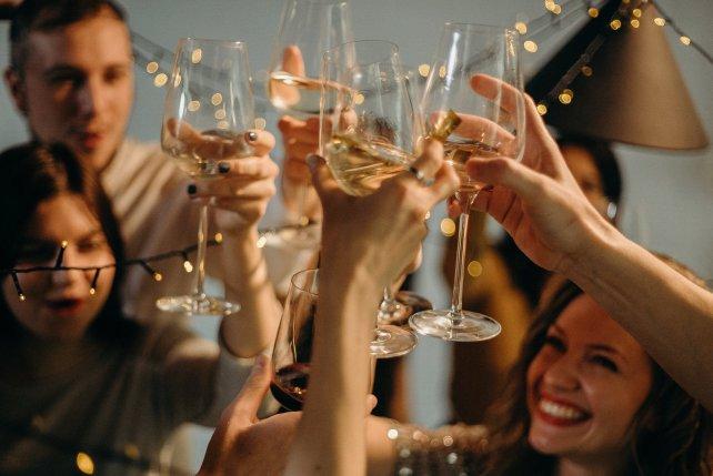 Gäste stoßen bei Party mit Gläsern an